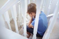 Niño trastornado del problema que se sienta en las escaleras imagen de archivo