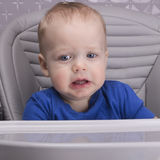 Niño trastornado en una silla del bebé que mira la cámara foto de archivo