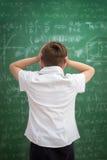 Niño trastornado que mira la pizarra por completo de fórmulas imagenes de archivo