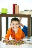 Niño travieso que come los dulces debajo de la tabla fotos de archivo