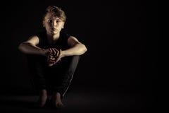 Niño triste asentado con los brazos alrededor de rodillas Imagenes de archivo
