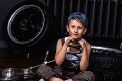 Niño triste cansado en el garaje entre los neumáticos imagenes de archivo