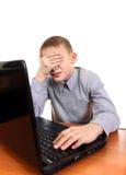 Niño triste con el ordenador portátil Imagenes de archivo