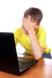 Niño triste con el ordenador portátil Imágenes de archivo libres de regalías