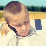 Niño triste con el teléfono móvil Imágenes de archivo libres de regalías