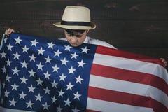 Niño triste con la bandera de los Estados Unidos Imagenes de archivo
