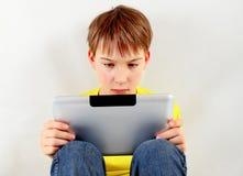 Niño triste con la tableta Foto de archivo libre de regalías