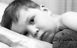 Niño triste con un oso de peluche Fotos de archivo