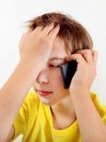 Niño triste con un teléfono Fotografía de archivo