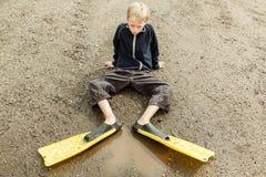 Niño triste en aletas del salto en el charco Foto de archivo