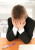 Niño triste en el escritorio Imagen de archivo libre de regalías
