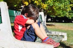 Niño triste en el parque, al aire libre Imagen de archivo