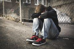 Niño triste en la calle de la ciudad Foto de archivo