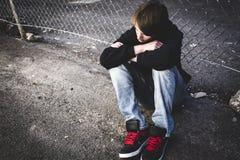 Niño triste en la calle de la ciudad Imagenes de archivo