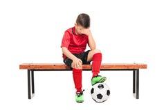 Niño triste en la sentada uniforme del fútbol en un banco Foto de archivo libre de regalías