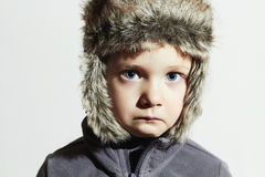 Niño triste en sombrero de piel Embroma estilo casual del invierno Little Boy Emoción de los niños Foto de archivo