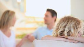 Niño triste en un sofá mientras que sus padres están discutiendo almacen de metraje de vídeo