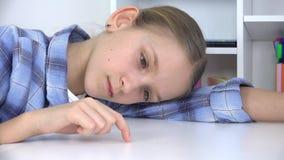 Niño triste, muchacha aburrida que juega los fingeres en el escritorio, niño infeliz subrayado que no estudia almacen de metraje de vídeo