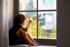 Niño triste, muchacho, sentándose en un escudo de la ventana Foto de archivo libre de regalías