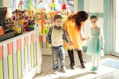 Niño triste que celebra a la madre para la mano en tienda de chucherías Foto de archivo