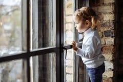 Niño triste que mira hacia fuera la ventana Foto de archivo