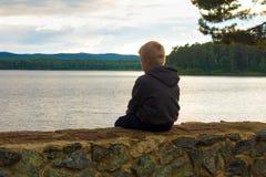 Niño triste que se sienta en el lago Imagenes de archivo