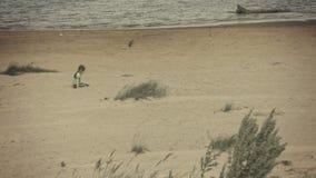 Niño triste que se sienta en una orilla del río almacen de metraje de vídeo