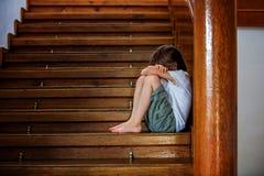 Niño triste, sentándose en una escalera en una casa grande, concepto para los BU foto de archivo