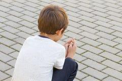 Niño triste, solo, decepcionado que se sienta solamente en la tierra al aire libre imagen de archivo libre de regalías
