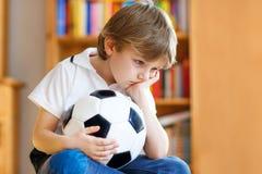 Niño triste y no feliz con fútbol sobre juego perdido del fútbol o de fútbol niño después de mirar el partido en la TV foto de archivo libre de regalías
