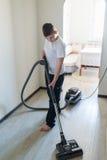 Niño usando aspirador en casa Foto de archivo