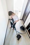Niño usando aspirador en casa Imágenes de archivo libres de regalías