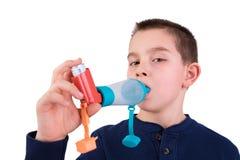 Niño usando el inhalador con el espaciador Foto de archivo libre de regalías