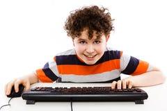 Niño usando el ordenador en el fondo blanco Imagen de archivo libre de regalías