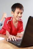 Niño usando el ordenador portátil Imagen de archivo