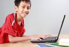 Niño usando el ordenador portátil Imagen de archivo libre de regalías