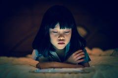 Niño usando la tableta en fondo oscuro del dormitorio Imagen de archivo