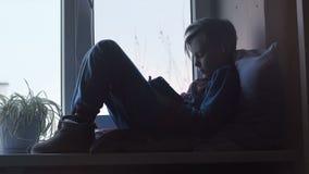 Niño usando la tableta en travesaño de la ventana metrajes