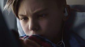 Niño usando la tableta en travesaño de la ventana almacen de video