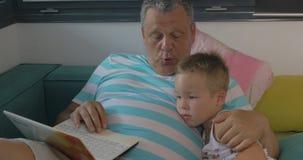 Niño y abuelo que usa el ordenador portátil en casa almacen de video