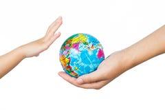 Niño y adulto que sostienen un globo del mundo en manos Foto de archivo