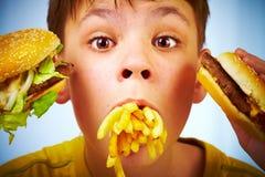 Niño y alimentos de preparación rápida. Fotografía de archivo
