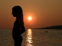 Niño y barco en puesta del sol en el mar Foto de archivo libre de regalías