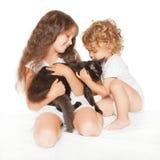 Niño y bebé que juegan con el gatito de Maine Coon Imagen de archivo