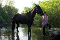 Niño y caballo en el río Fotos de archivo libres de regalías