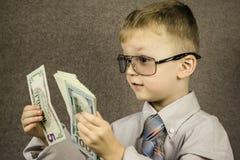Niño y dólares fotos de archivo