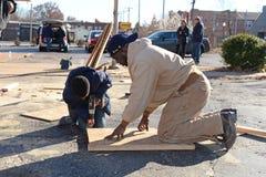 Niño y hombre que trabajan para subir encima de negocio en Ferguson Imágenes de archivo libres de regalías