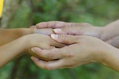 Niño y madre que celebran las manos Imagen de archivo
