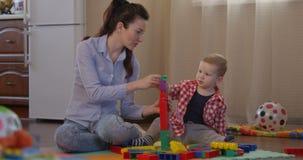 Niño y madre que construyen la torre grande que juega a juegos movKid y madre que construyen la torre grande que juega a juegos y almacen de video