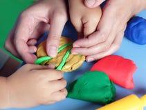 Niño y madre que juegan con el playdough Imagenes de archivo